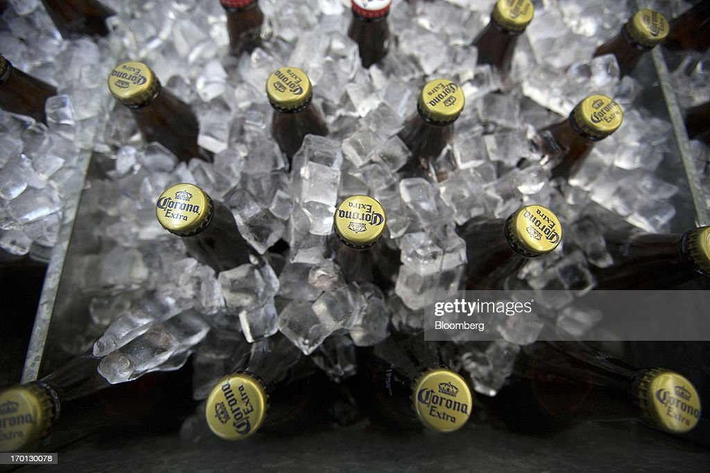 Bottles of Grupo Modelo SAB's Corona brand beer sit in a cooler with ice at a store in Mexico City, Mexico, on Thursday, June 6, 2013. Heineken NV and Grupo Modelo SAB, the dominant brewers in Mexico with brands such as Dos Equis and Corona, are nearing the end of an almost three-year-old government antitrust probe. Photographer: Susana Gonzalez/Bloomberg via Getty Images