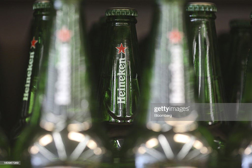 Bottles of Heineken lager beer, produced by Heineken NV, sit on display inside a supermarket in London, U.K., on Friday, Feb. 8, 2013. Britain's economy will grow more slowly this year than previously forecast and stagnation may persist, according to the National Institute of Economic and Social Research. Photographer: Chris Ratcliffe/Bloomberg via Getty Images