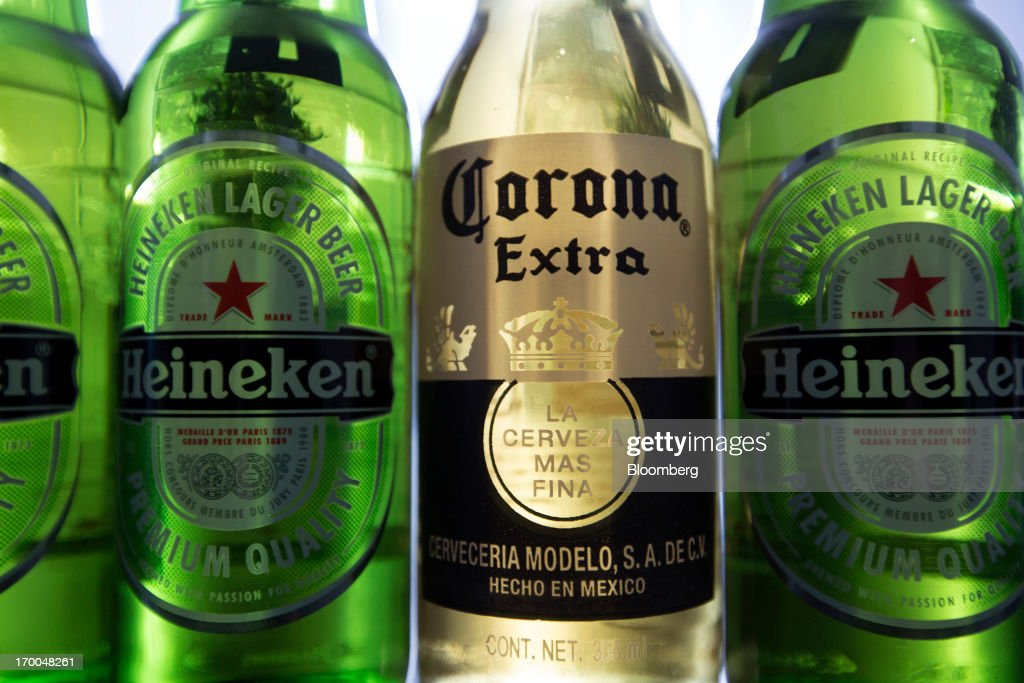 Bottles of Heineken NV beer and a bottle of Grupo Modelo's Corona beer are arranged for a photo in Mexico City, Mexico, on Thursday, June 6, 2013. Heineken NV and Grupo Modelo SAB, the dominant brewers in Mexico with brands such as Dos Equis and Corona, are nearing the end of an almost three-year-old government antitrust probe. Photographer: Susana Gonzalez/Bloomberg via Getty Images
