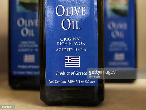 Bottles of imported Greek olive oil with 'Product of Greece' info displayed on their labels are seen on a shelf at the Greek Columbus Foods market...