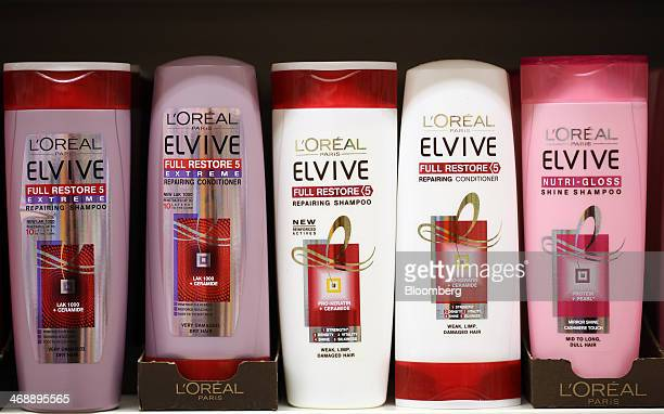 Bottles of L'Oreal Elvive hair shampoos and conditioners manufactured by L'Oreal SA sit displayed for sale on a shelf inside a supermarket in London...