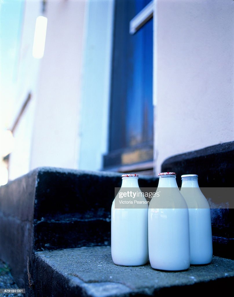 Bottles of milk on steps of house, England : Stock Photo