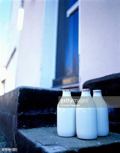Bottles of milk on steps of house, England