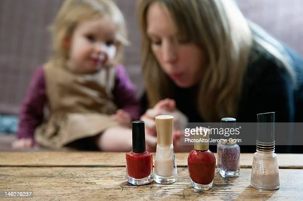 Bottles of nail polish, mother blowing on young daughter's toes in background