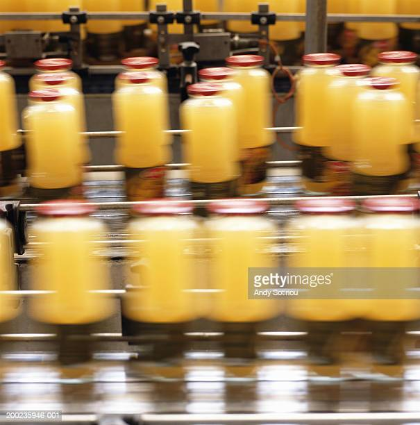 Bottles of orange juice on conveyor belt (blurred motion)