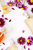 Bottles of perfume and flowers on white background, copy space