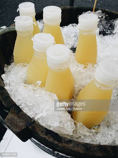 Bottles Of Pineapple Juice With Ice In Container