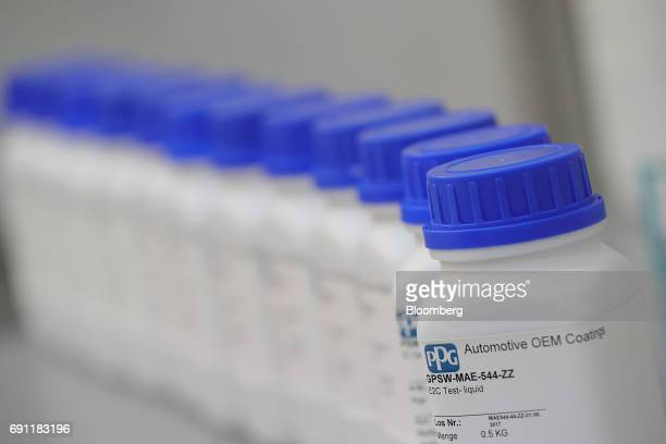 Bottles of PPG clearcoat coating liquid stand inside PPG Industries Inc's automotive coating's technical center in Ingersheim Germany on Thursday...