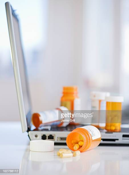 Bottles of prescription pills on laptop