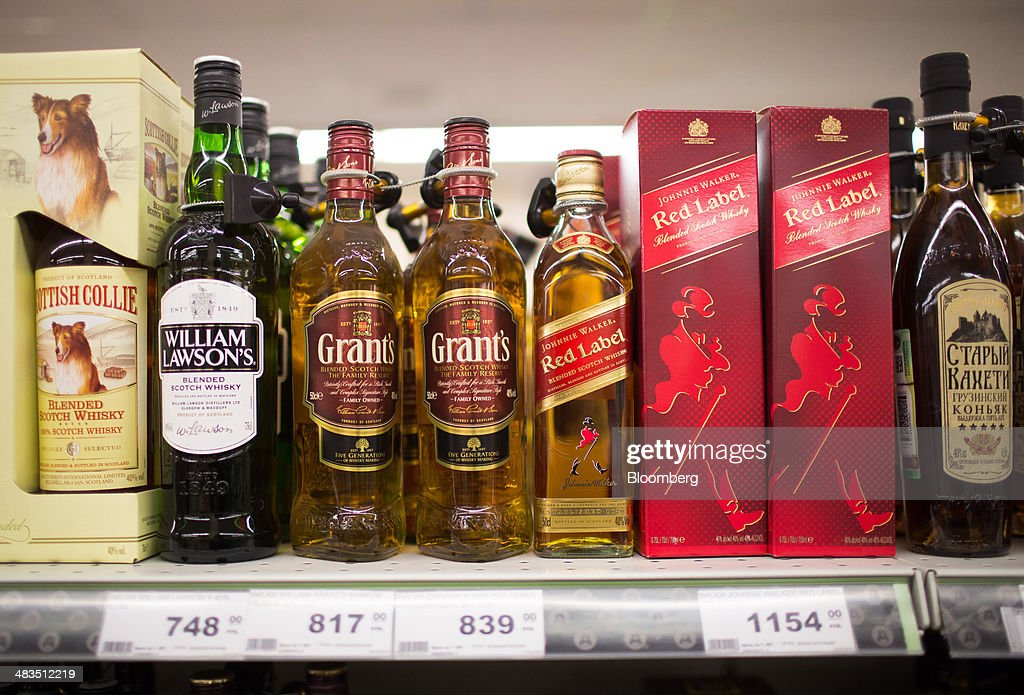 Bottles of Scotch whiskies including, from left, British Collie, William Lawson's, Grants, Johnnie Walker Red Label brands stand on display inside a Dixy supermarket operated by OAO Dixy Group in Moscow, Russia, on Tuesday, April 8, 2014. Suppliers suffering from ruble depreciation this quarter are urging retailers to increase prices. Photographer: Andrey Rudakov/Bloomberg via Getty Images