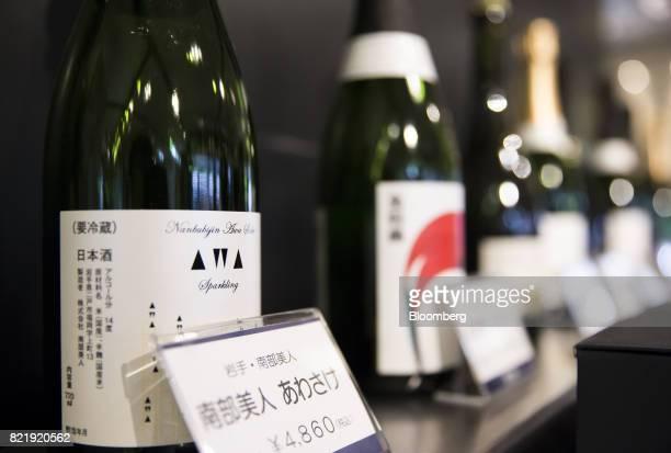 Bottles of sparkling sake including the NanbuBijin Awasake Sparkling brewed by NanbuBijin Co left sit on display in the Japan Awasake Association...