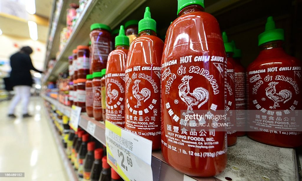 Bottles of Sriracha chili sauce are displayed on shelves as people shop inside a supermarket in Rosemead, California, on October 31, 2013. A Los Angeles Superior Court judge refused to halt operations of Sriracha's chili sauce plant in Irwindale, California, due to complaints from neighbors about the sting in the air when the peppers are mashed. A November 22 hearing has been scheduled on whether to issue a preliminary injunction after the city of Irwindale sued the sauce-maker Huy Fong Foods Inc., on October 28 claiming it a public nuisance. The Rosemead-based company, founded by Vietnamese immigrant David Tran in 1980 in Los Angeles Chinatown, uses fresh chili's which are mashed during a two-month autumn period. AFP PHOTO/Frederic J. BROWN