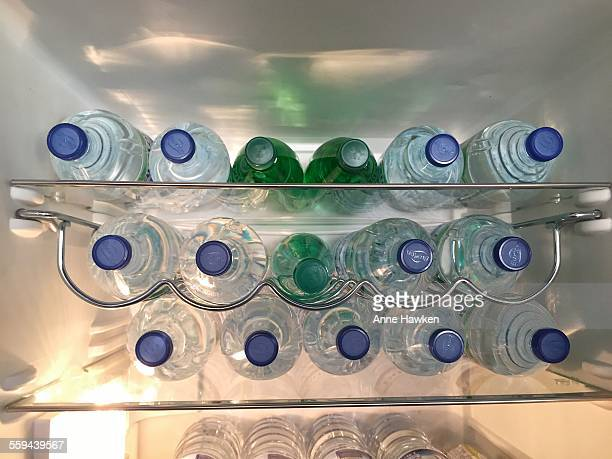 Bottles of still and sparkling water inside a domestic fridge