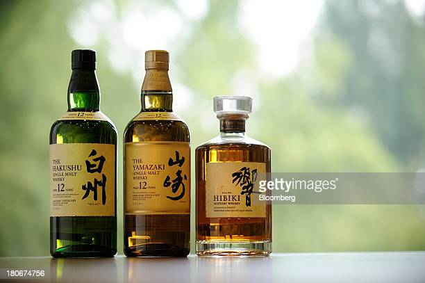 Bottles of Suntory Holdings Ltd's Hakushu whisky from left Yamazaki whisky and Hibiki whisky are arranged for a photograph at the company's Yamazaki...