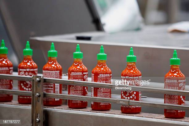 Bottles of the Sriracha hot sauce travel down a conveyor belt to be boxed for shipment at the Huy Fong Foods Inc facility in Irwindale California US...