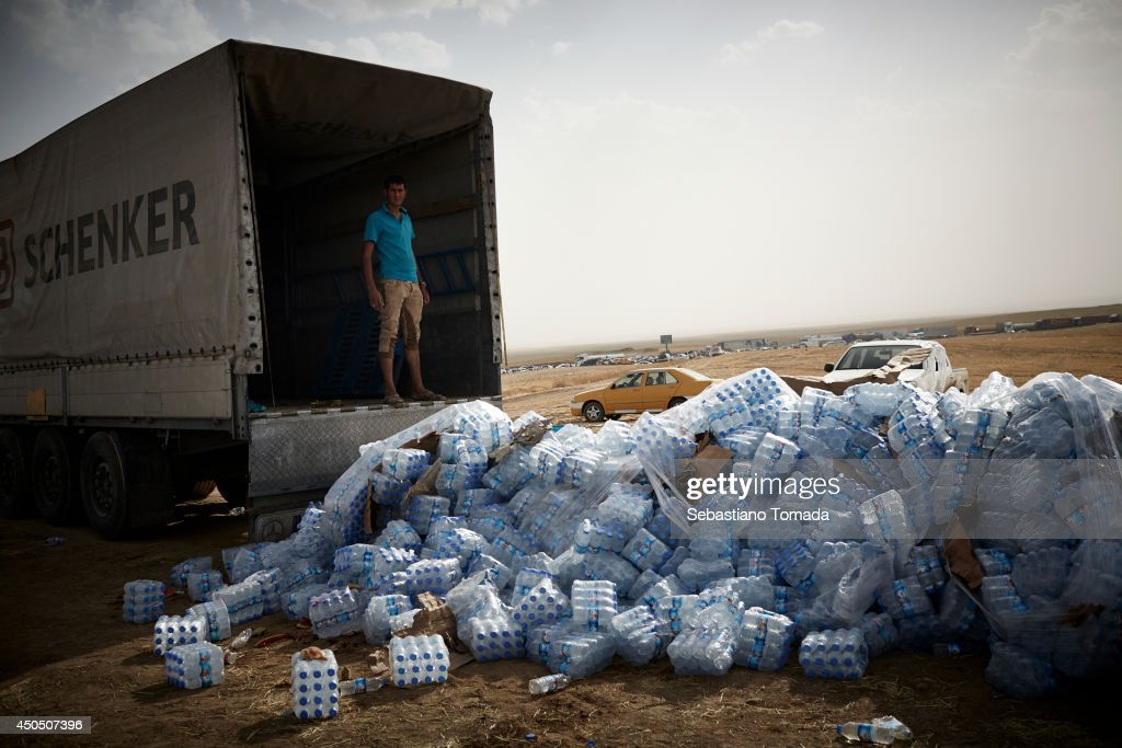 Bottles of water are dropped off in Kalak at a Kurdish checkpoint in northern Iraq for the refugees fleeing from ISIS militants. June 12, 2014.