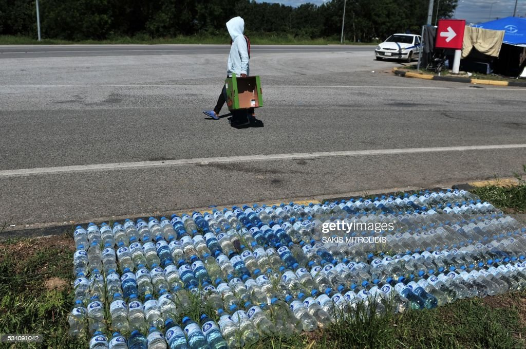 Bottles of water are exposed to the sun to be used as hot water at a makeshift camp set near a gas station some 20 km from the Greek-Macedonian border, on 25 May, 2016 in Polykastro. In an operation which began shortly after sunrise on May 24, hundreds of Greek police began evacuating the sprawling camp which is currently home to 8,400 refugees and migrants, among them many families with children, an AFP correspondent said. At its height, there were more than 12,000 people crammed into the site, many of them fleeing war, persecution and poverty in the Middle East and Asia, with the camp exploding in size since Balkan states began closing their borders in mid February in a bid to stem the human tide seeking passage to northern Europe. / AFP / SAKIS
