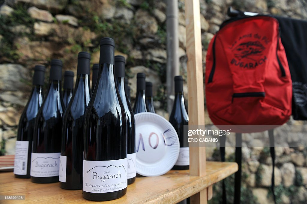 Bottles of wine and backpacks are proposed to visitors at the 'Bug' boutic' (Bugarach shop) of the 'Amis du Pic' (Peak's friends) association, on December 20, 2012 in the French southwestern village of Bugarach, near the 1,231 meter high peak of Bugarach - one of the few places on Earth some believe will be spared when the world allegedly ends according to claims regarding the ancient Mayan calendar, on December 21. French authorities have pleaded with New Age fanatics, sightseers and media crews not to converge on the tiny village. The slogan on the bottle reads : 'if only one remains, I will be that one'.