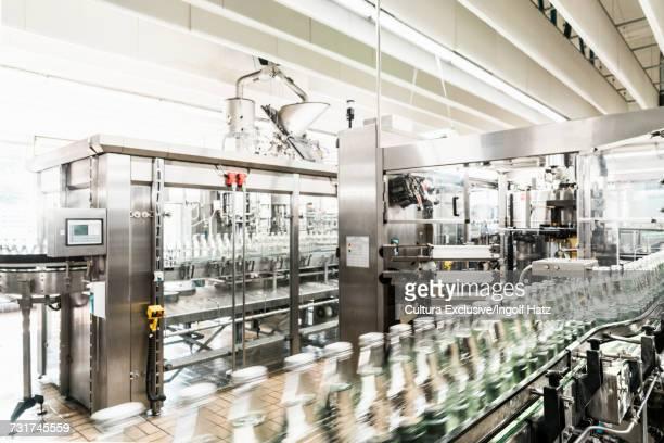 Bottles on conveyor belt in bottling facility, bottling mineral spring water