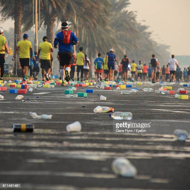 Bottles On Street Against People Running In Marathon