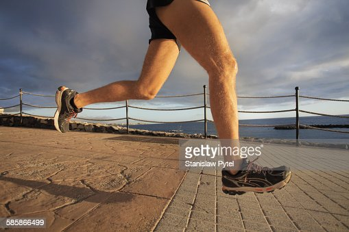 Bottom view on legs of running man near ocean