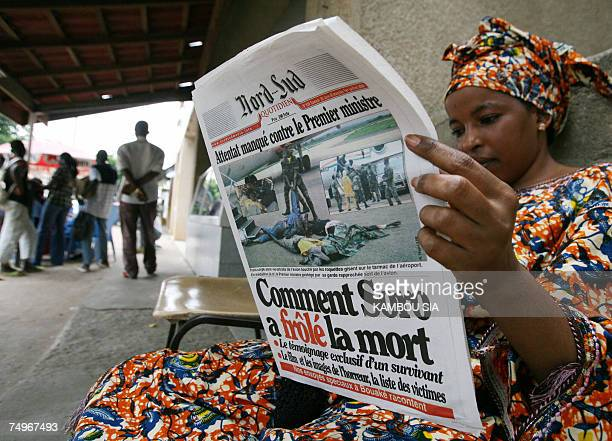 A woman reads a newspaper in Bouake 30 June 2007 a day after four people died and 10 were injured when Prime Minister Guillaume Soro's aircraft was...