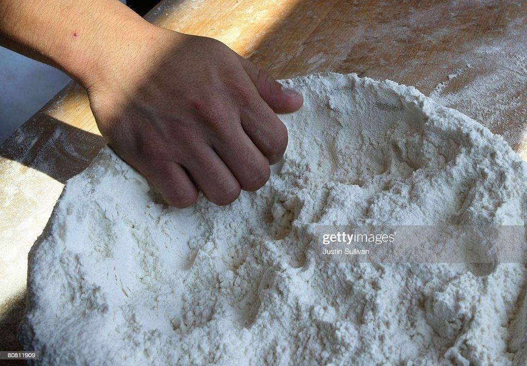 Boudin Bakery bread baker Calixta Luna reaches into a bowl of flour as he rolls dough for sourdough bread at Boudin Bakery April 21 2008 in San...