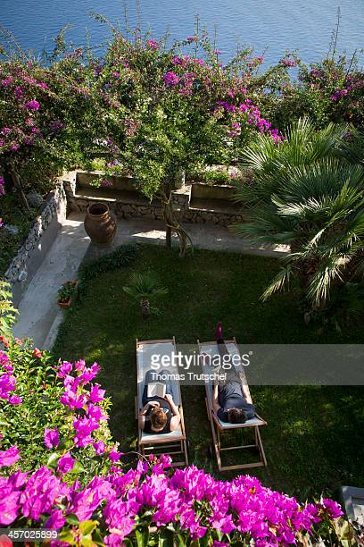 A bougainvillea framed view from above of a woman and a man each lying on a sun lounger reading a book in a garden in the Campania region pictured on...