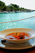 Stewed Bouillabaisse Soup with Delicious Seafood closeup in White Bowl on Blurred Sea Harbor background Outdoors