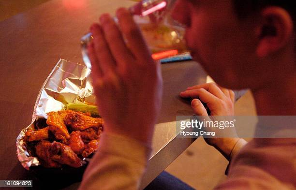 Boulder CO_February 8 James Rachlin political science major student of CU Boulder is having a beer with chicken wings at Thunderbird Burgers BBQ in...