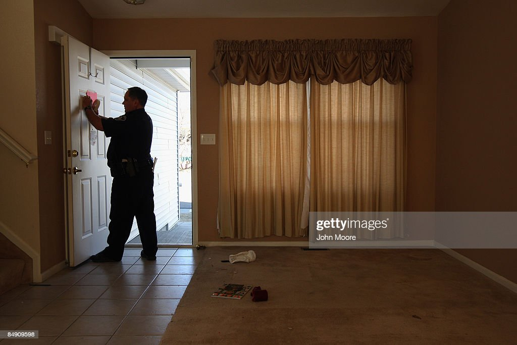 Boulder County sheriff's deputy Rick Ferguson tapes a 'no trespass order' on the front door of a home that was forclosed February 18, 2009 in Longmont, Colorado. The tenants had stopped paying their mortgage payments two months before and then moved out just prior to the eviction. President Barack Obama announced a 75 billion dollar Homeowner Stability Initiative today in Mesa, Arizona, designed to keep roughly 8 million homeowners that are in danger of foreclosure in their homes.