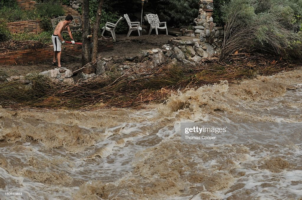 A Boulder resident tries to make a barrier to keep flood waters from coming over the edge during Severe flooding due to heavy rains and swollen rivers caused damage on roads and homes September 13, 2013 in Boulder, Colorado. The historic flooding forced thousands to evacuate the area and more rain is predicted through the weekend.