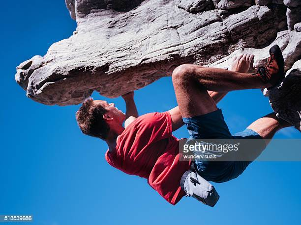 Bouldering rock climber hanging beneath extreme overhang against blue sky