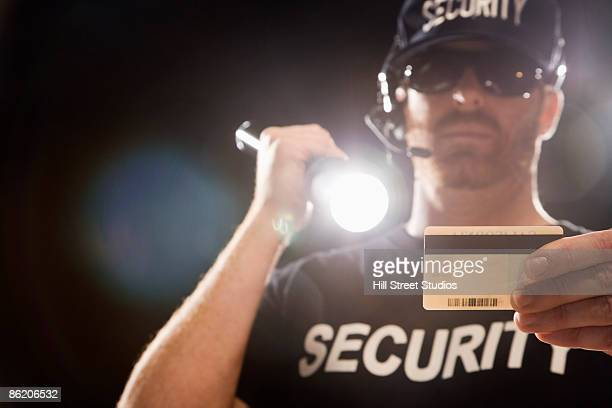 Bouncer checking identification with flashlight