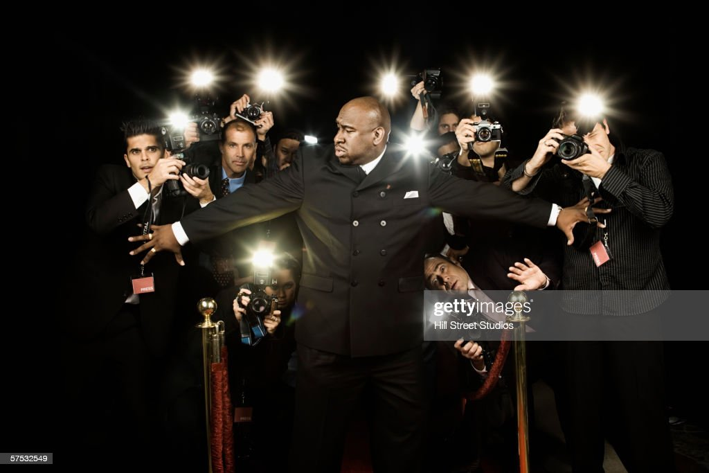 Bouncer holding photographers back : Stock Photo