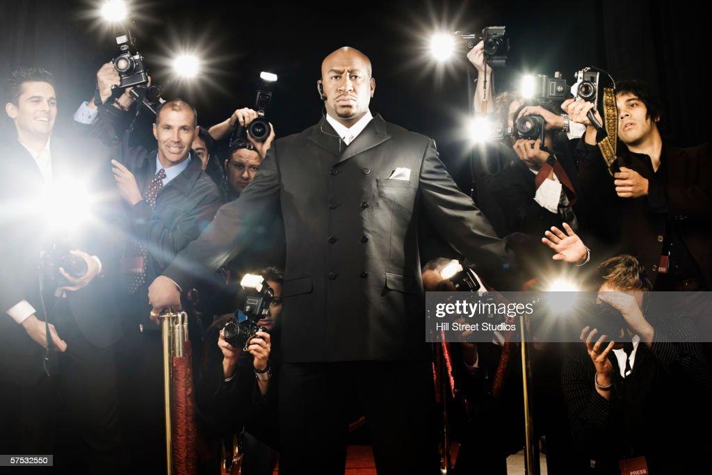 Bouncer holding photographers back : Stock Photo