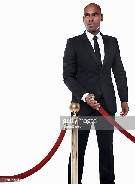 Bouncer in suit with crowd control post against white