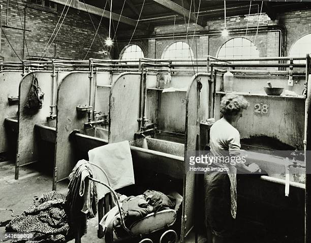 Boundary Street Area Laundry Bethnal Green London 1964 A woman washes some clothes in a deep sink while more clothes are piled on a pram behind her...