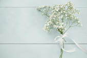 Little baby's breath bouquet on wooden bckground with copyspace