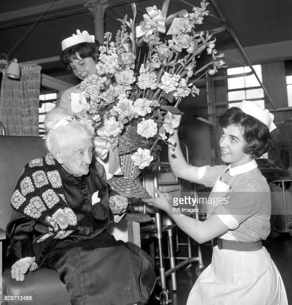 A bouquet for her 108th birthday is shown to Mrs Elizabeth Kemsley by staff nurses Gillian Taylor and Margaret Turner at St Pancras Hospital London