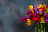 bouquet of bright spring flowers on dark gray background with copy space