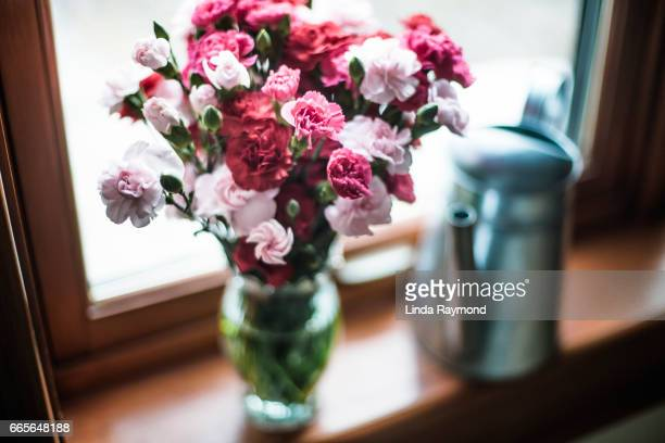 Bouquet of flowers and a watering can by a window