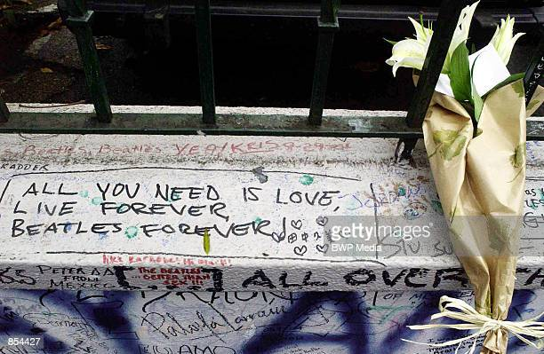 A bouquet of flowers are left on a graffitiridden wall outside the Abbey Road Studios for former Beatles singer and guitarist George Harrison...