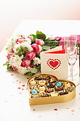 Bouquet of flowers by heart shaped box of chocolates and  card