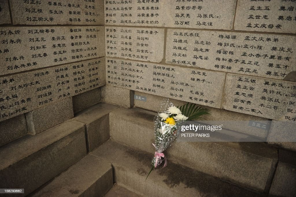 A bouquet of flowers is placed by a Nanjing massacre survivor on a wall listing the names of victims, on the 75th anniversary of the Nanjing massacre at the Memorial Museum in Nanjing on December 13, 2012. Air raid sirens sounded in the Chinese city of Nanjing on December 13 as it marked the 75th anniversary of the mass killing and rape committed there by Japanese soldiers -- with the Asian powers' ties at a deep low. AFP PHOTO/Peter PARKS