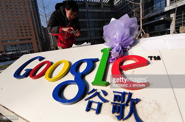 A bouquet of flowers lay upon the company logo as a man photographs a commentary placed beneath a rock outside the Google China headquarters in...