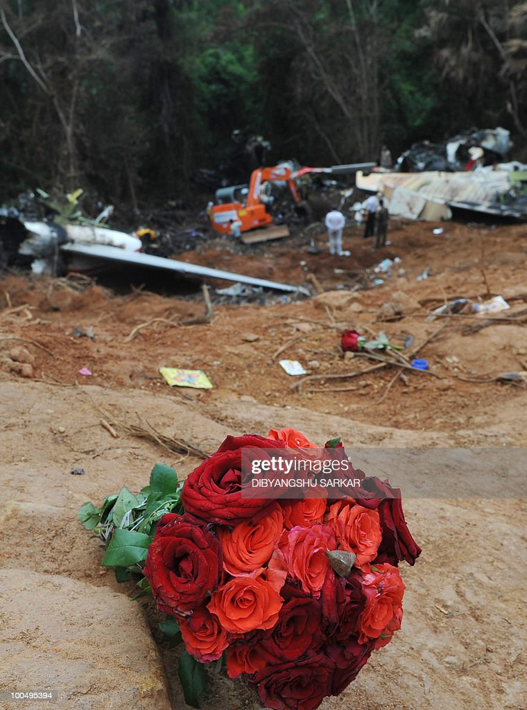 A bouquet of flowers, left by an unidentified mourner, is seen at the crash site of the doomed Air India Express flight 812 during recovery operations for the 'black box' digital flight recorder in Mangalore on May 25, 2010. Investigators recovered May 25 the 'black box' digital flight recorder that holds crucial clues to the crash of an Air India Express plane in southern India that killed 158 people. The discovery followed an intense three-day search that began hours after the Boeing 737-800, flying from Dubai to the city of Mangalore, overshot the runway May 22, plunged into a gorge and burst into flames.AFP PHOTO/Dibyangshu Sarkar