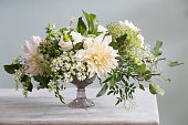 An elaborate bouquet of flowers in  a vase.  All the flowers are white with some greenery mixed in.  The vase sits on a marble surface and in front of a blank gray background.  The lighting is natural