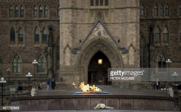 A bouquet of flowers sits in front of the eternal flame in front of Canada's House of parliament in Ottawa Thursday evening October 23 one day after...