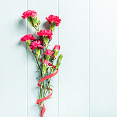 Bouquet of pink carnation on light turquoise wooden background. Top view with copy space.
